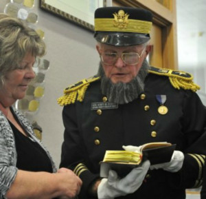 Picture of Gerry Olsen enacting Henry Martyn Robert presenting newest edition of book to Ventura library