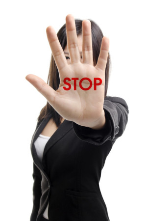woman holding up hand with stop written on palm